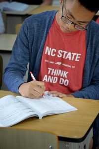 Chemical engineering student Elton Luong of Charlotte takes notes during Chinese language class.